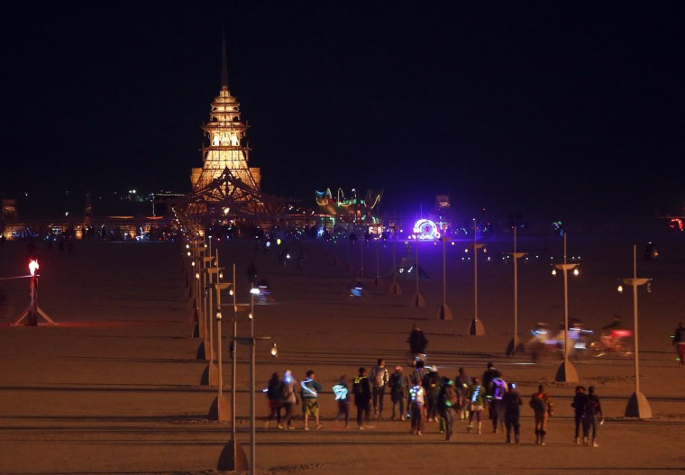 People walk towards the Temple of Juno, which is alit at night. (Jim Urquhart/Reuters)