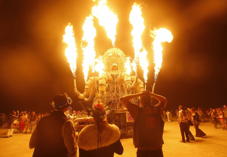 """Participants watch the flames from El Pulpo Mecanico during the Burning Man 2012 """"Fertility 2.0"""" arts and music festival in the Black Rock Desert of Nevada. (Jim Urquhart/Reuters)"""