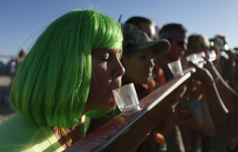 """A woman of the playa name """"Indigo"""" participates in a drinking game during the Burning Man 2012 . (Jim Urquhart/Reuters)"""
