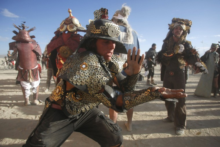 "Mark Gower, dressed as a samurai, dances at sunrise during the Burning Man 2012 ""Fertility 2.0"" arts and music festival in the Black Rock Desert of Nevada. (Jim Urquhart/Reuters)"