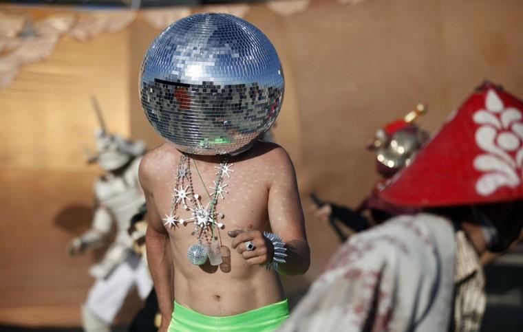"Ciberfy, his playa name, dances at sunrise during the Burning Man 2012 ""Fertility 2.0"" arts and music festival in the Black Rock Desert of Nevada. (Jim Urquhart/Reuters)"