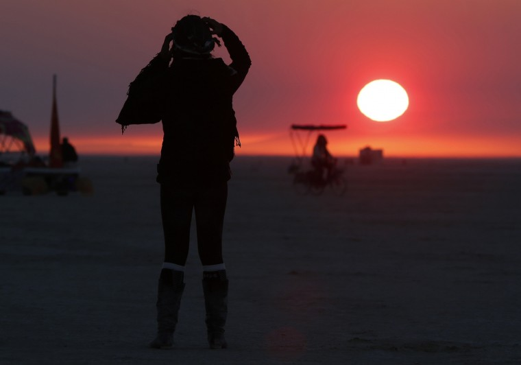 """Libriel Padilla watches the sunrise as it is obscured by smoke from the western wildfire during the Burning Man 2012 """"Fertility 2.0"""" arts and music festival. (Jim Urquhart/Reuters)"""