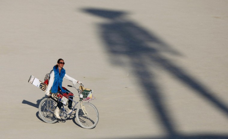 "A participant rides past the shadow of the Man during the Burning Man 2012 ""Fertility 2.0"" arts and music festival in the Black Rock Desert of Nevada. (Jim Urquhart/Reuters)"