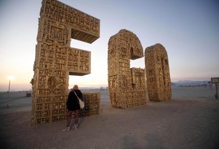 "Ruth Kidd explores the art piece ""Ego"" before sunrise. (Jim Urquhart/Reuters)"