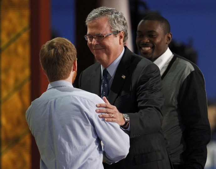 Former Florida Governor Jeb Bush (C) embraces teacher Sean Duffy as student Frantz Placide (R) looks on during an address to the final session of the Republican National Convention in Tampa, Florida. (Joe Skipper/Reuters)
