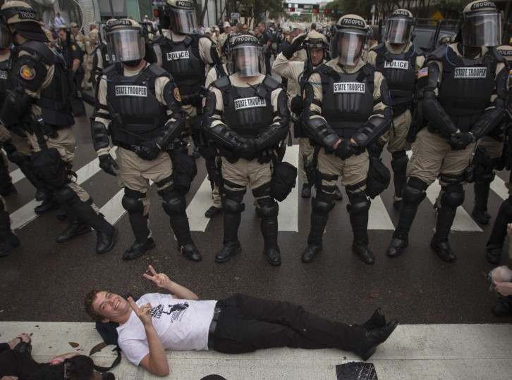 An activist lies in front of a police-line during a protest on the streets outside the Republican National Convention in Tampa Florida August 27, 2012. Republicans have cut their Tampa, Florida, convention from the traditional four days to three because of a threatening storm, just as they did four years ago when a hurricane hit Louisiana. (Adrees Latif/Reuters)