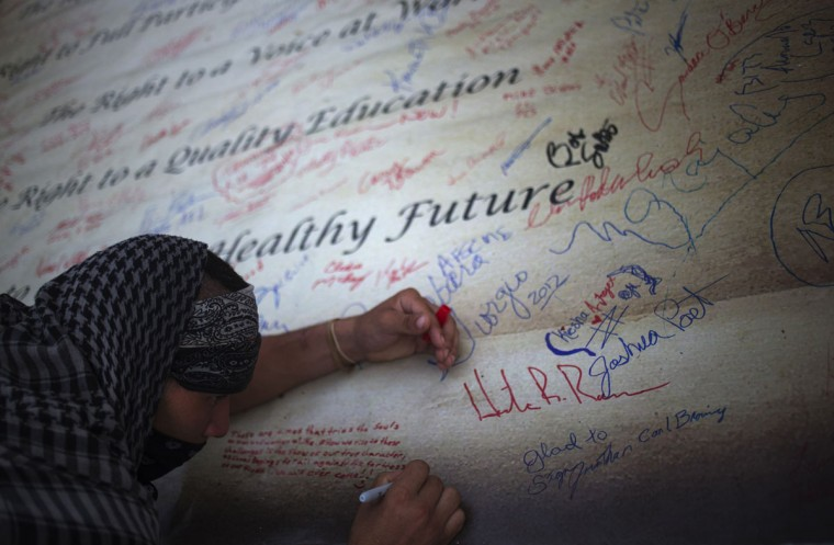 A demonstrator signs a banner promoting workers' rights during a pro-union rally outside the site of the Republican National Convention in Tampa, Florida August 29, 2012. (Adrees Latif/Reuters)