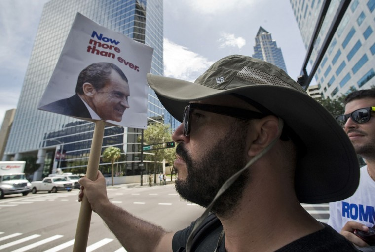 A Republican party supporter holds a vintage Nixon campaign poster on a downtown street corner outside the Republican National Convention in Tampa, Florida. (Steve Nesius/Reuters)
