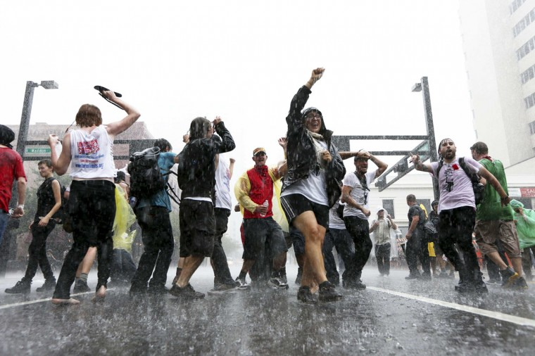 Protesters dance during a sudden, heavy rainstorm while protesting outside the Republican National Convention in Tampa, Florida August 27, 2012. (Philip Andrews/Reuters)