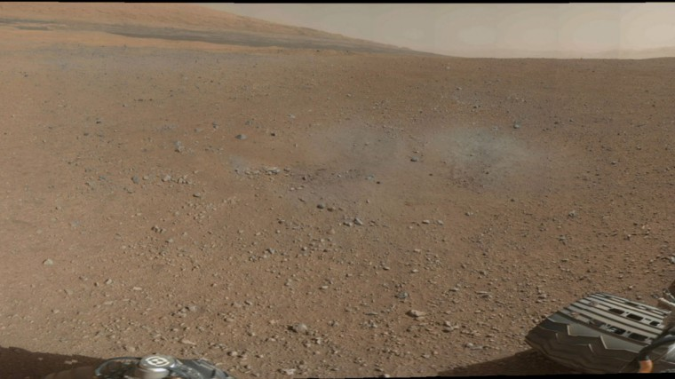 August 9, 2012: This is a portion of the first color 360-degree panorama from NASA's Curiosity rover in Mars made up of thumbnails, which are small copies of higher-resolution images. The mission's destination, a mountain at the center of mountain at the center of Gale Crater called Mount Sharp, can be seen in the distance, to the left, beginning to rise up. Blast marks from the rover's descent stage are in the foreground. (NASA/JPL-Caltech/MSSS/Handout/Reuters)
