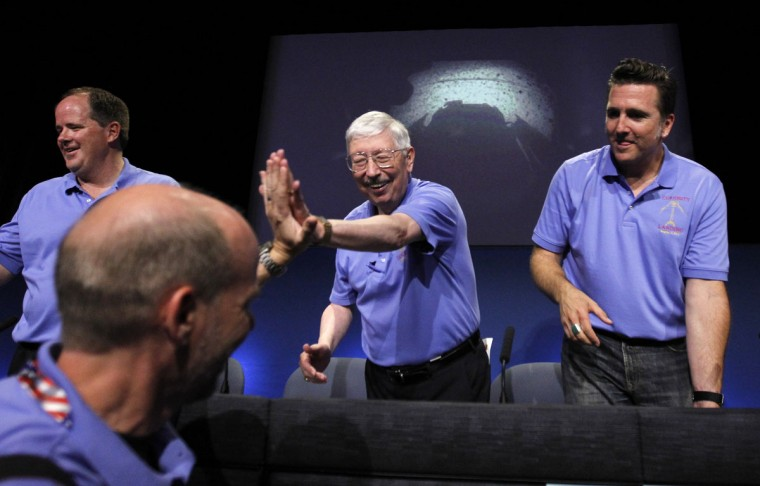 August 5, 2012: Mars Science Laboratory Curiosity rover flight controllers and managers (L-R) Richard Cook, Pete Theisinger and Adam Steltzner congratulate their team members after a successful rover landing, during a news conference at NASA's Jet Propulsion Lab in Pasadena, California. One of the first images from the rover is projected on background. (Fred Prouser/Reuters)