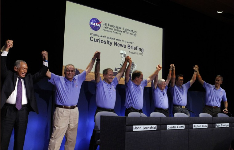 August 5, 2012: Mars Science Laboratory Curiosity rover flight controllers and managers (L-R) NASA Administrator Charles Bolden, JPL director Charles Elachi, NASA associate administrator John Grunsfeld, Richard Cook, Pete Theisinger, Adam Steltzner and John Grotzinger stand as they celebrate after a successful rover landing, during a news conference at NASA's Jet Propulsion Lab in Pasadena, California. (Fred Prouser/Reuters)