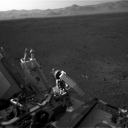 August 9, 2012: This full-resolution image taken August 7, 2012 shows part of the deck of NASA's Curiosity rover on Mars taken from one of the rover's Navigation cameras looking toward the back left of the rover. On the left of this image, part of the rover's power supply is visible. To the right of the power supply can be seen the pointy low-gain antenna and side of the paddle-shaped high-gain antenna for communications directly to Earth. The rim of Gale Crater is the lighter colored band across the horizon. The effects of the descent stage's rocket engines blasting the ground can be seen on the right side of the image, next to the rover. (NASA/JPL-Caltech/Handout/Reuters)