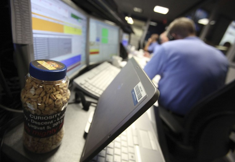 August 5, 2012: A specially marked jar of peanuts sits on a workstation inside the Spaceflight Operations Facility for NASA's Mars Science Laboratory Curiosity rover at Jet Propulsion Laboratory in Pasadena, California. In a long-standing tradition before critical mission events dating back to the 1960's, the control room crew will eat some good luck peanuts. (Brian van der Brug/Pool/Reuters)