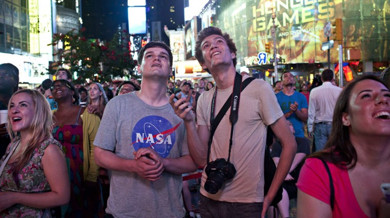 August 6, 2012: Jasper Goldberg (front, 2nd L), 22, and Andreas Bastian (front, 2nd R), 22, watch a live broadcast of the NASA Mission Control center, as the planetary rover Curiosity lands on Mars, in Time Square, in New York. (Andrew Burton/Reuters)