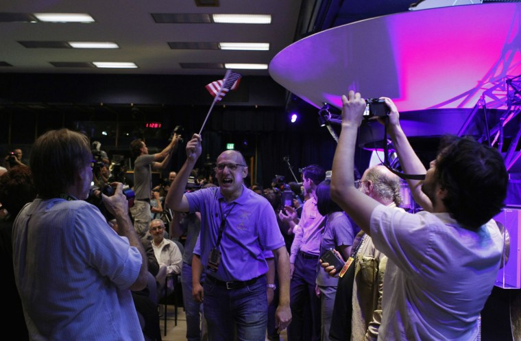 August 5, 2012: Mars Science Laboratory Curiosity rover team member Miguel San Martin (C) waves an American flag after a successful rover landing, as he arrives for a news conference at NASA's Jet Propulsion Lab in Pasadena, California. (Fred Prouser/Reuters)