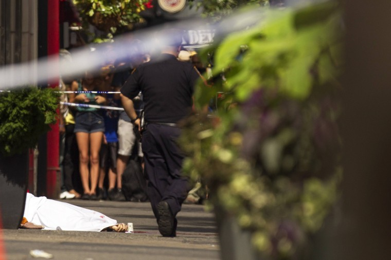 A hand sticks out from underneath a sheet covering a body on 33rd St after a shooting at the Empire State Building in New York. (Lucas Jackson/Reuters)