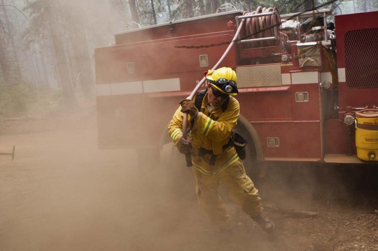 Firefighter Tim Nolen pulls a fire hose to put out a spot fire, while battling the Chips fire near Greenville, California August 20, 2012. The fire has forced evacuations and burned over 47,000 acres in Northern California. (Max Whittaker/Reuters photo)
