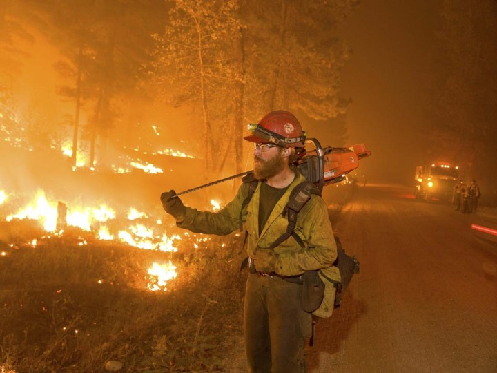 A firefighter carries a chainsaw while watching a burn operation in Boise National Forest near the community of Featherville, Idaho. (Kari Greer/U.S. Forest Service)