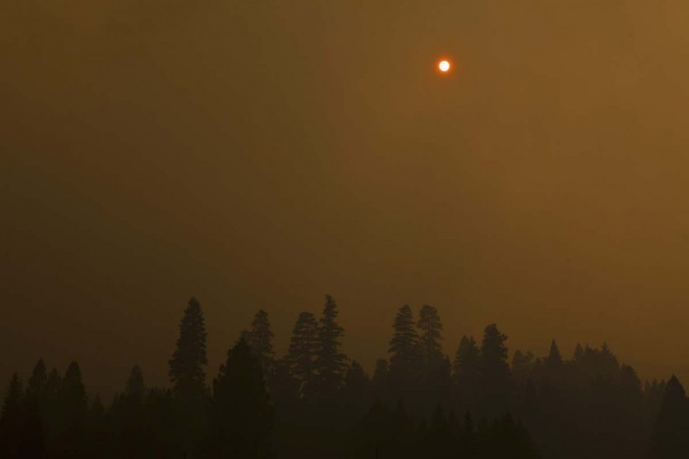 The sun is obscured over the Chips fire near Greenville, California. The fire has forced evacuations and burned over 47,000 acres in Northern California. (REUTERS/Max Whittaker)