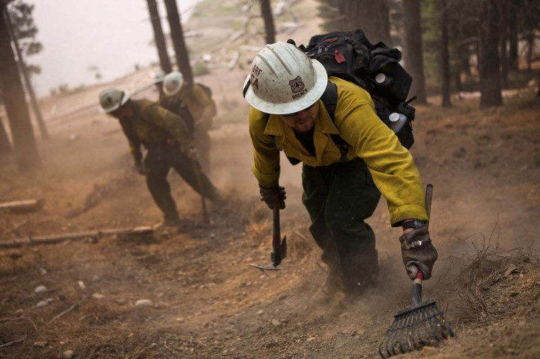 A US Forest Service fire crew digs a fire line on the Chips fire near Greenville, California. The fire has forced evacuations and burned over 47,000 acres in Northern California. (REUTERS/Max Whittaker)