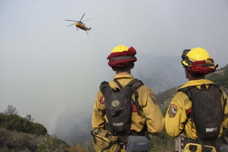Firefighters look on as a helicopter aids firefighting efforts at the Ponderosa Fire near Red Bluff, California. (REUTERS/Mary Slosson)