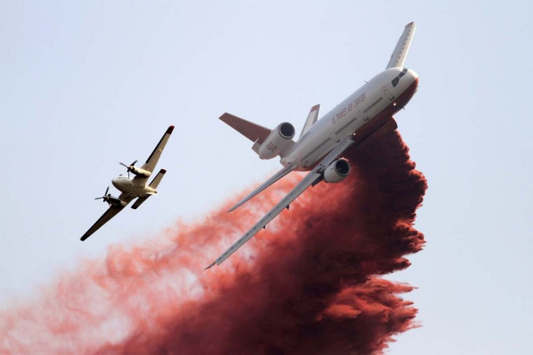 A firefighting tanker plane drops fire retardant on homes threatened by the Taylor Creek Fire outside Cle Elum, Washington. Wildfires roared out of control across the sun-scorched U.S. West on Wednesday and threatened to roll into two small towns in Idaho as firefighters managed to partially dampen a monster blaze that has destroyed 60 homes in Washington state. (Robert Sorbo/Reuters photo)