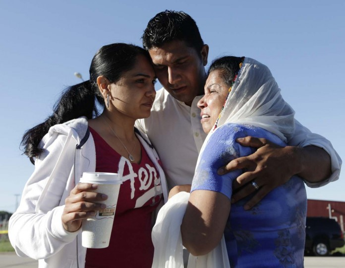 OAK CREEK, WI - AUGUST 6: Mourners, including Amardeep Kaleka (C) whose father, temple president Satwant Kaleka, was killed, cry outside the scene of a mass shooting in Oak Creek, Wisconsin, August 6, 2012. The gunman who killed six people at a Sikh temple in southern Wisconsin was a former U.S. serviceman, a law enforcement official said on Monday, and a monitor of extremists said the shooter had links to racist groups. (John Gress/Reuters)