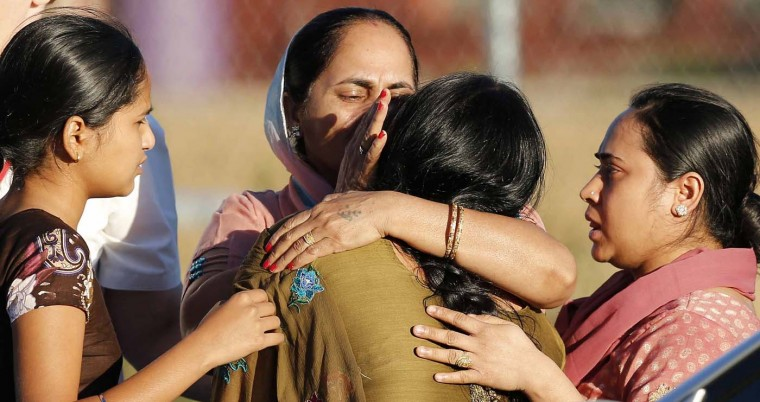 OAK CREEK, WI - AUGUST 5: A distraught women is comforted outside of the Sikh temple in Oak Creek, Wisconsin August 5, 2012. A shooting during Sunday services at the temple left at least seven people dead, including a gunman, and at least three critically wounded, police and hospital officials said. (Tom Lynn/Reuters)