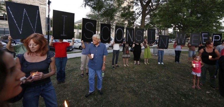 AUGUST 5: People hold a large sign while attending a candle light vigil at Cathedral Square in downtown Milwaukee, Wisconsin August 5, 2012. A shooting during Sunday services at the Sikh temple in a nearby Oak Creek left at least seven people dead, including a gunman, and at least three critically wounded, police and hospital officials said. (Tom Lynn/Reuters)