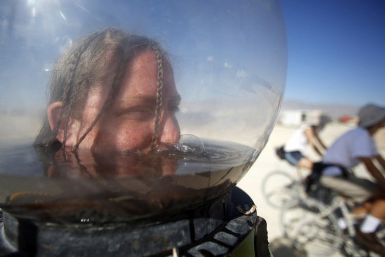 "Hallie McConlogue stays cool partially submerged in a fishbowl helmet during the Burning Man 2012 ""Fertility 2.0"" arts and music festival in the Black Rock Desert of Nevada. (Jim Urquhart/Reuters)"