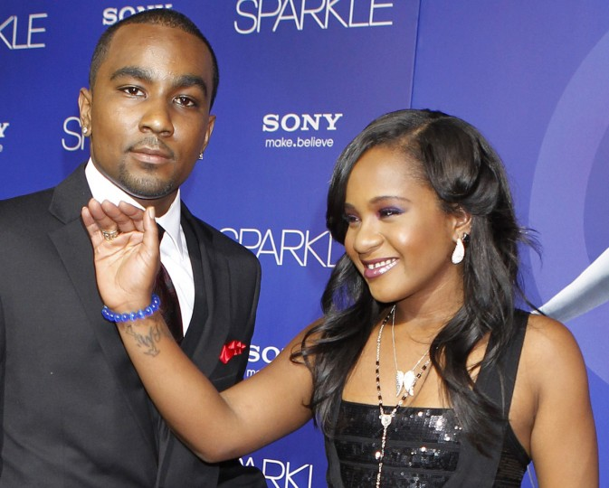 "Bobbi Kristina Brown, daughter of the late singer Whitney Houston, reveals a tattoo with the initials ""W H"" as she waves while arriving with boyfriend Nick Gordon at the premiere of the new film ""Sparkle"" starring Jordin Sparks and the late Whitney Houston in Hollywood August 16, 2012. (Fred Prouser/Reuters)"