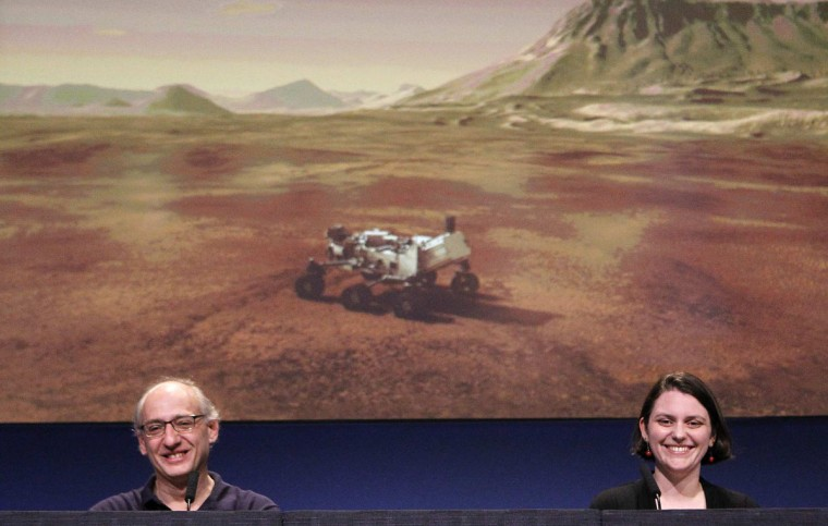 August 6 2012: Mars Science Laboratory team member Miguel San Martin, left, and Sarah Milkovich speak during a press briefing at the Jet Propulsion Laboratory in La Ca-ada Flintridge after NASA's successful MSL Curiosity landing. Animation of the MSL Curiosity is on screen in the background. (Brian van der Brug/Los Angeles Times)