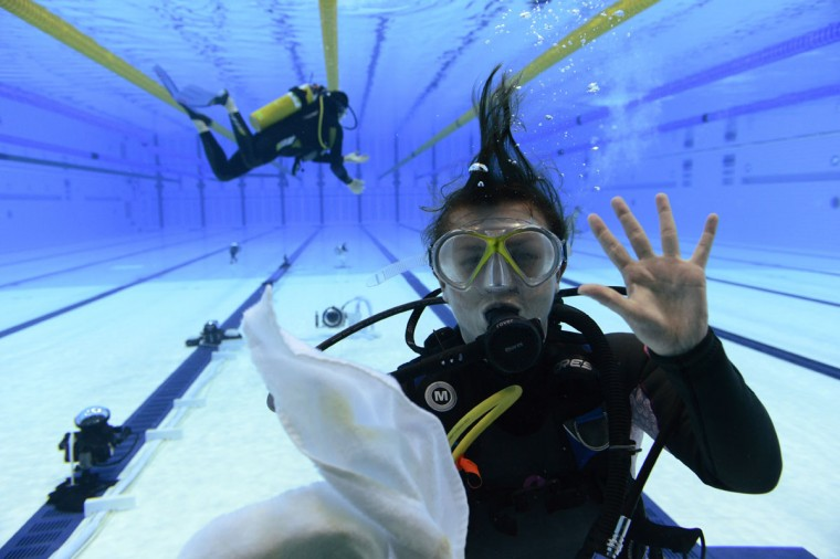 A technician in dive gear clears a camera window in the pool during the London 2012 Olympic Games at Aquatics Centre. (Andrew P. Scott/USA TODAY Sports)