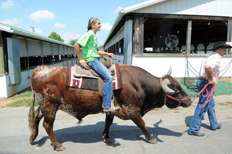 Day 2: MacKenzie Ridgely, 16, of Cooksville rides a texas longhorn guided by her uncle Randy Ridgely in the Grand Opening Parade. (Brian Krista/Patuxent Homestead)