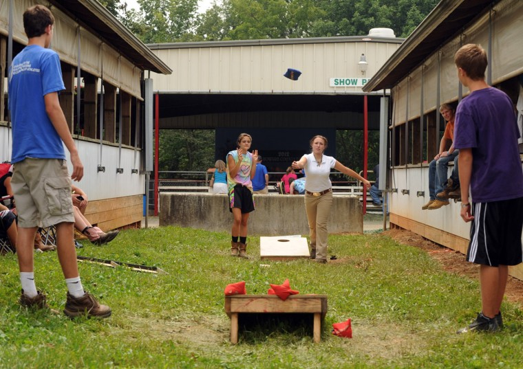Day 4: McKenzie Ridgely, left, and Courtney Moulton, both of Libertytown, compete in a game of cornhole with Chris Moxley, foreground left, and Chris Buckley, both of West Friendship, between animal barns. (Brian Krista/Patuxent Homestead)