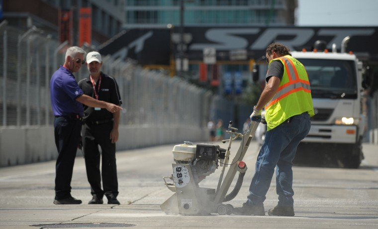 A worker grinds the concrete on the Grand Prix of Baltimore course by the light rail tracks at Pratt and Howard streets. Cars were catching air as they passed over the tracks. (Gene Sweeney Jr./Baltimore Sun Photo)