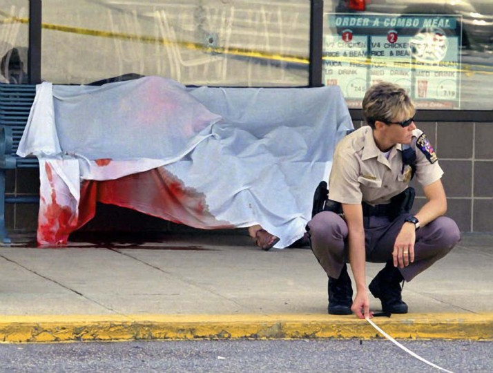 Five people shot dead, apparently at random and with frightening precision, over a 16 hour period in various Montgomery county locations within close proximity to each other. Pictured, a police officer takes measurements in front of the remains of a hispanic woman killed on a bench in front of a fast food restaurant near a post office in Leisure World plaza, on Georgia avenue. (Bill O'Leary/The Washington Post)