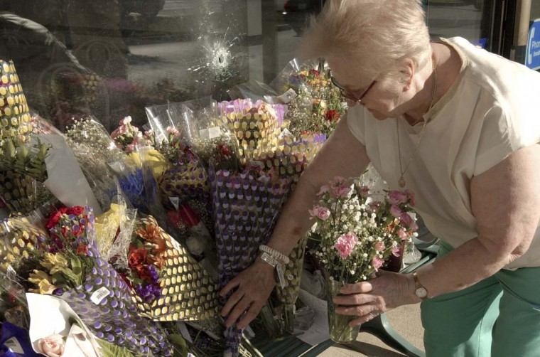 Martha Brescha adds flowers to a bench below a bullet hole in a window in a strip mall October 5, 2002 in Silver Spring, Maryland. The bullet hole is from the sniper who is being blamed for six shootings in Montgomery County, Maryland and Washington, D.C. The sniper is still at large. (Stefan Zaklin/ Getty Images)