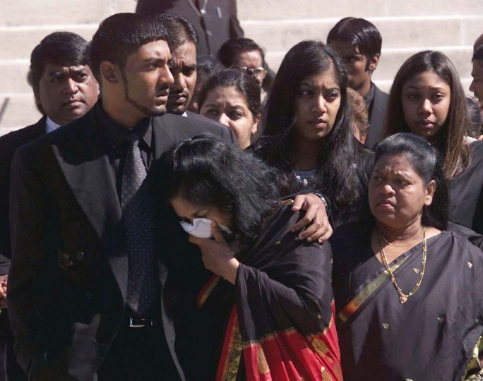 Andrew Walekar (L) comforts his mother Margaret, as pallbearers place the casket of 54-year-old Prem Kumar Walekar into a hearse at Sligo Seventh Day Adventist Church in Takoma Park, Maryland following funeral service, October 6, 2002. Walekar was shot and killed October 3 as part of a 36 hour shooting spree that left six dead in Washington area. Police still have no suspects. (Brendan McDermid/Reuters photo)