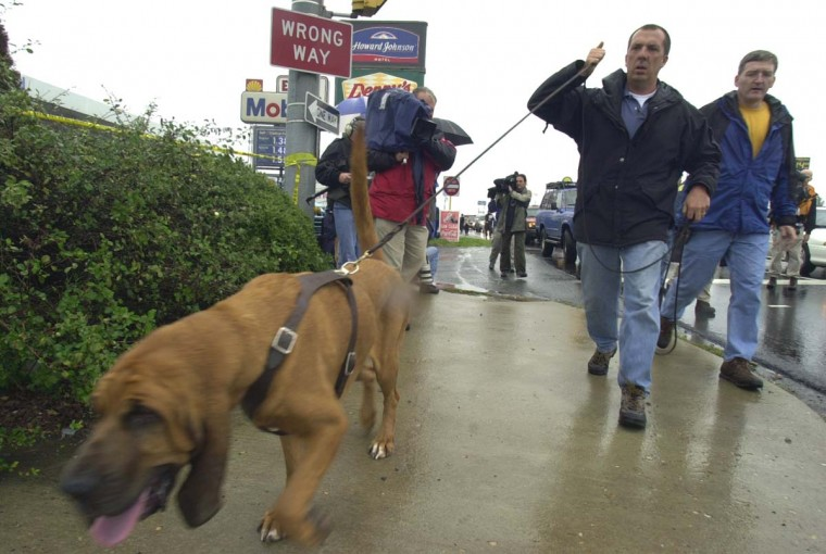 Police lead a bloodhound as they investigate a fatal shooting at an Exxon gas station, in Fredericksburg, Va., Friday Oct. 11, 2002. Police were scouring the area looking for clues. It wasn't immediately clear if the shooting was linked to nine sniper attacks that have left seven people dead in the Washington area. (Steve Helber/AP photo)