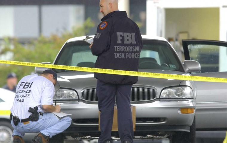 Law enforcement agents look for clues in the sniper shooting of a man at Four Mile Fork Exxon in Fredricksburg, Virginia on Friday morning. The victim was fueling his car around 9:30 a.m. (Doug Kapustin/Baltimore Sun)