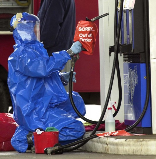 A worker in protective clothing cleans the gas pump at the scene of a fatal shooting at an Exxon station in Fredericksburg, Va., Saturday Oct. 12, 2002. Police confirmed that the shooting was connected to the recent area sniper shootings. (Steve Helber/AP Photos)