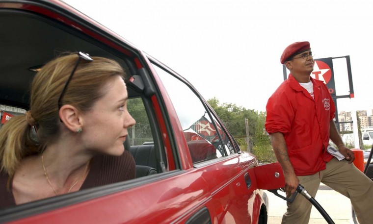 Monique McNamara, of Alexandria Va., looks at Raul Lopez, of the New York chapter of the Guardian Angels, as he pumps gas for her at a gas station in Alexandria, Va., Saturday Oct. 12, 2002, a day after a sniper attacked for the tenth time at a gas station in Fredericksburg, Va. (Evan Vucci/Getty Images)