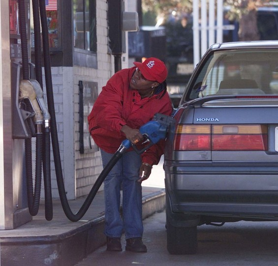 An unidentified woman crouches while pumping gas at a gas station near Route 95 in Alexandria, Virginia, October 14, 2002. Four of the 10 sniper shootings have taken place at gas stations including the most recent one that took place in Spotsylvania County, Virginia. The search for the Washington area sniper continues. (Brendan McDermid/Reuters photo)