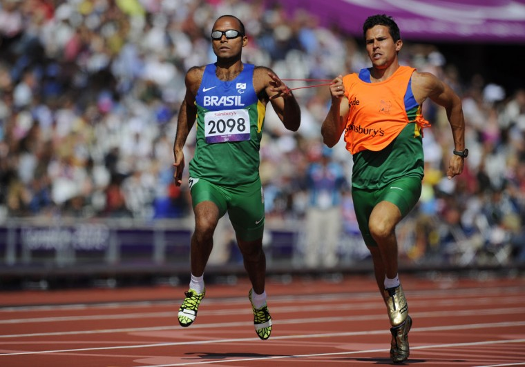 Brazil's Felipe Gomes (L) and guide Leonardo Souza Lopes (R) compete in the men's 200m T11 semi-final during the athletics competition at the London 2012 Paralympic Games in the Olympic Stadium in east London on September 4, 2012. (Glyn Kirk/AFP/Getty Images)