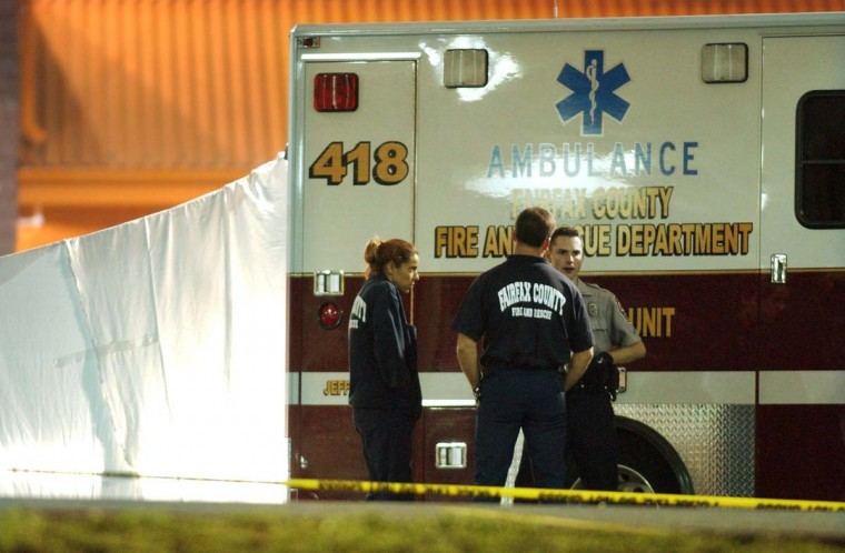 "Paramedics and a police officer stand near the body of Linda Franklin, 47, of Arlington, VA (behind shroud) after she was fatally shot in the head Monday night outside of a Home Depot. The bullet was linked to the ""beltway sniper"" the following morning. (David Hobby/Baltimore Sun)"