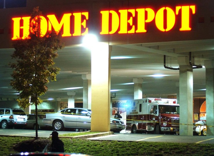 """A paramedic stands near the body of Linda Franklin, 47, of Arlington, VA (behind shroud at ambulance) after she was fatally shot in the head Monday night outside of a Home Depot. The bullet was linked to the """"beltway sniper"""" the following morning. (David Hobby/Baltimore Sun)"""
