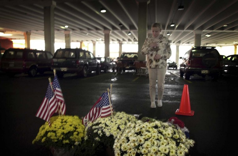 A memorial has been erected in the parking garage of the Home Depot in Seven Corners Shopping Center, in Falls Church, Va. the site of the most recent shooting perpetrated by the Washington area sniper. Jeannie Yarush, of Dale City, VA, who knew the victim, Linda Franklin, leaves a note at the site of her killing. They were friends for about six years and used to go tubing together on the Shenandoah River. (André F. Chung/Baltimore Sun)