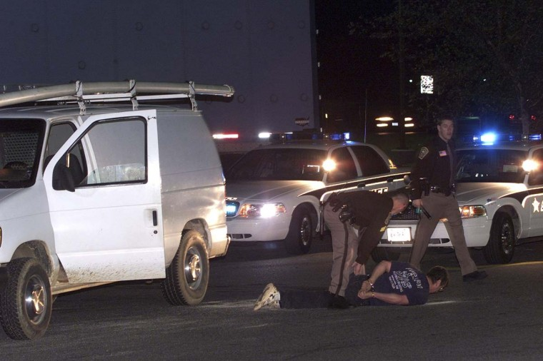 An unidentified man lies handcuffed on the ground next to his white van at a gas station in Stafford, Virginia, October 19, 2002. Law enforcement are stopping and handcuffing all drivers in white vans that fit a description in the current Washington area sniper attacks. Police reported Saturday that a person was shot and wounded in Ashland, Virginia, located 90 miles (145 km) south of the U.S. capital, but authorities said they did not know whether the incident was linked to the recent sniper shootings in the Washington area. (Brendan McDermid/Reuters photo)